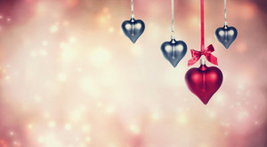 Hanging heart shaped ornaments on abstract pink lights background