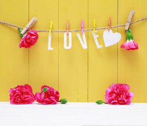 Hanging Love letters with pink carnation flowers over yellow wooden wall