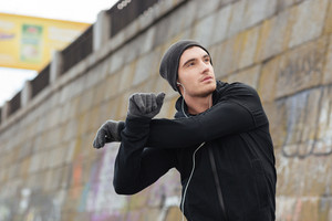 Hansome young man in hat and gloves standing and exercising outdoors