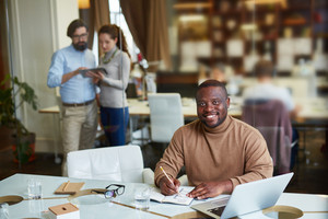 Happy African-American businessman planning work in office