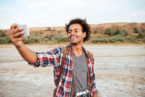 Happy african american man standing and taking selfie with cell phone outdoors