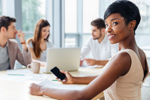 Happy african american young businesswoman using blank screen smartphone on business meeting
