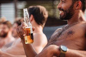 Happy african american young man relaxing and drinking beer with friends