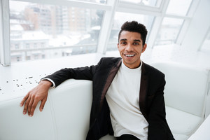 Happy african business man in black suit sitting on sofa in office and looking at camera