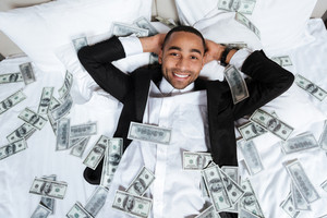 Happy African man in suit lying on bed in hotel room with falling money and looking at camera