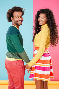 Happy african young couple holding hands and looking back over bright colorful background