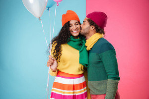 Happy african young couple in hats and scarves with balloons hugging and kissing