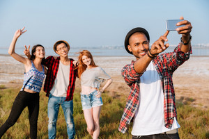 Happy african young man standing and taking selfie with his friends outdoors
