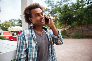 Happy african young man standing and talking on cell phone outdoors
