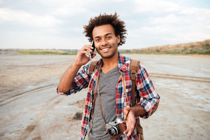 Happy african young man with vintage photo camera talking on mobile phone outdoors