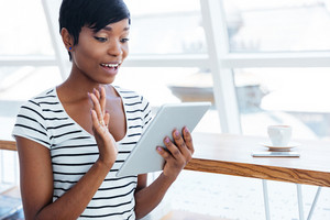 Happy afro american businesswoman holding tablet computer and waving in office
