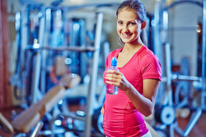 Happy and fit girl with bottle of water looking at camera