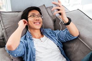 Happy asian man in shirt with phone on sofa. listening music