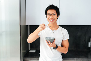 Happy asian man with cereal in the kitchen. front view