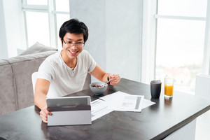 Happy asian man working and eating by the table. with tablet, juice and documents