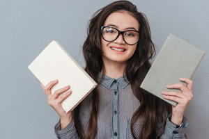 Happy Asian woman holding books in hands and looking at camera. Isolated gray background