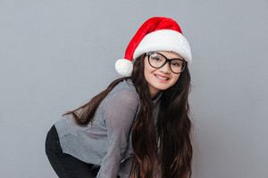 Happy Asian woman in christmas hat posing in studio and looking at camera. Isolated gray background