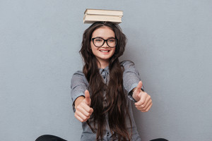 Happy Asian woman in glasses with books on head showing thumbs up at camera. Isolated gray background