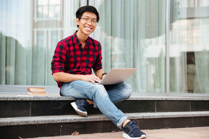 Happy asian young man in plaid shirt using laptop outdoors