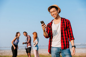 Happy asian young man standing and using mobile phone while his friends talking outdoors