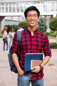 Happy asian young man student in glasses and plaid shirt with backpack standing outdoors