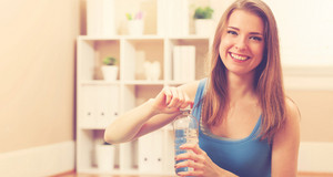 Happy athletic woman with a bottle of water in her home studio