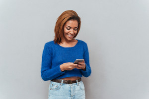 Happy attractive african woman in sweater and jeans writing message on phone in studio. Isolated gray background
