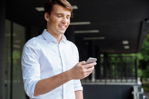 Happy attractive young businessman using smartphone and smiling near business center