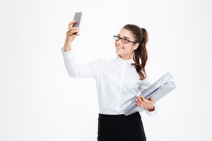 Happy attractive young businesswoman in glasses taking selfie using smartphone over white background