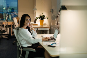 Happy attractive young businesswoman working with laptop at the table in office