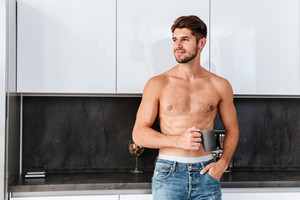 Happy attractive young man drinking coffee on the kitchen at home