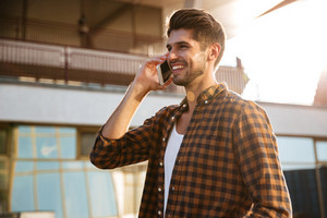 Happy attractive young man in checkered shirt talking on cell phone outdoors