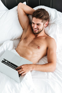 Happy attractive young man lying in bed and using laptop