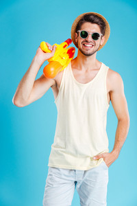 Happy attractive young man standing and holding water gun