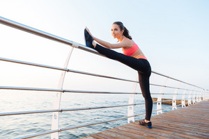 Happy attractive young sportswoman standing and stretching legs on pier