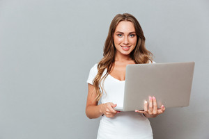 Happy attractive young woman standing and holding laptop over gray background