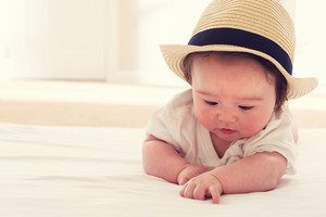 Happy baby boy with a straw hat