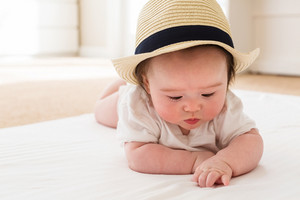 Happy baby boy with a straw hat