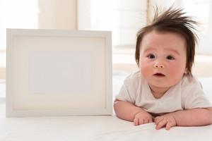 Happy baby boy with a white photo frame