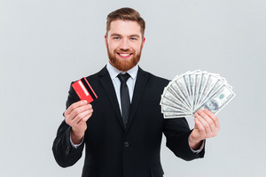 Happy bearded business man in black suit holding credit card and money in hands. Isolated gray background