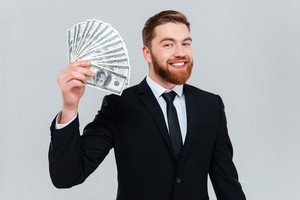 Happy bearded business man in black suit holding money in hand and looking at camera. Isolated gray background