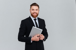 Happy bearded business man in black suit holding tablet computer and looking at camera in studio. Isolated gray background