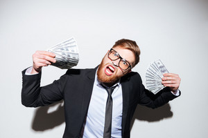 Happy bearded business man in glasses and suit with money in hands as well as with open mouth. Isolated gray background