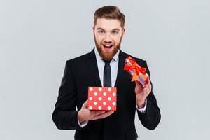 Happy bearded business man in suit opening gift and looking at camera. Isolated gray background