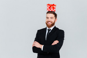 Happy bearded business man in suit with gift on head and arms crossed looking at camera. Isolated gray background