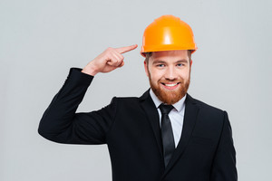 Happy bearded engineer in black suit pointing at helmet and looking at camera. Isolated gray background