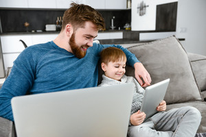 Happy bearded father dressed in blue sweater hugging his son and using laptop while his son playing with tablet computer
