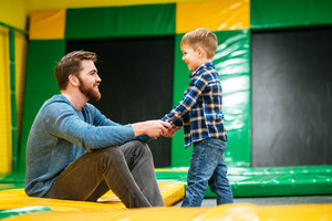 Happy bearded father sitting and playing with his little son at indoor amusement park