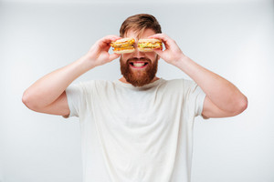 Happy bearded man covering eyes with hamburgers isolated on white background