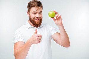 Happy bearded man holding green apple and showing thumbs up gesture isolated on white background